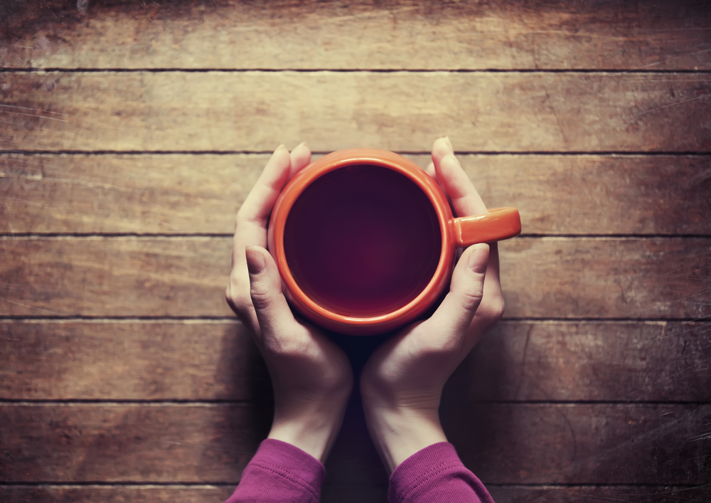 two hands holding tea cup startup