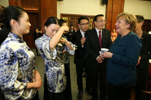 Demonstrating tea customs to Angela Merkel